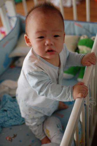 Daryl Chang standing in crib