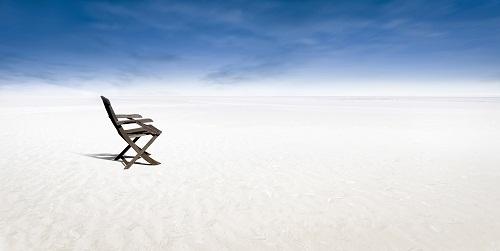 chair on empty beach by Fred Fokkelman